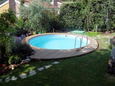 Realizzazione piscina - Vasca in vetro resina posata su letto di ghiaia, rifinita con pedane in legno di teak raccordate con camminamenti in pietra